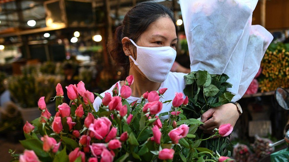 A woman wearing a mask carrying flowers in Hanoi