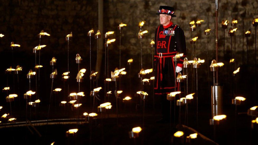 A Yeoman Warder stands among lit torches that are part of the installation Beyond the Deepening Shadow at the Tower of London November 4, 2018