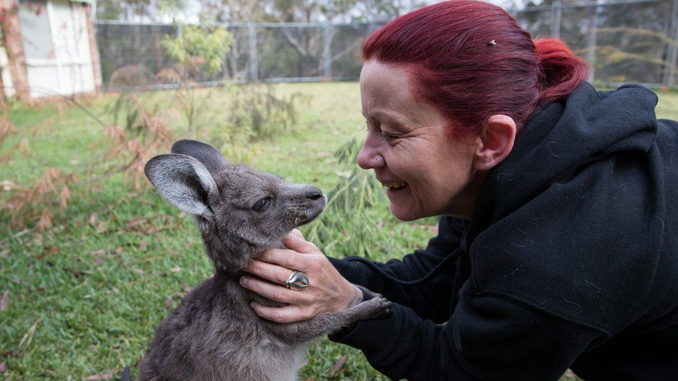 Rae Harvey pats a relaxed-looking joey