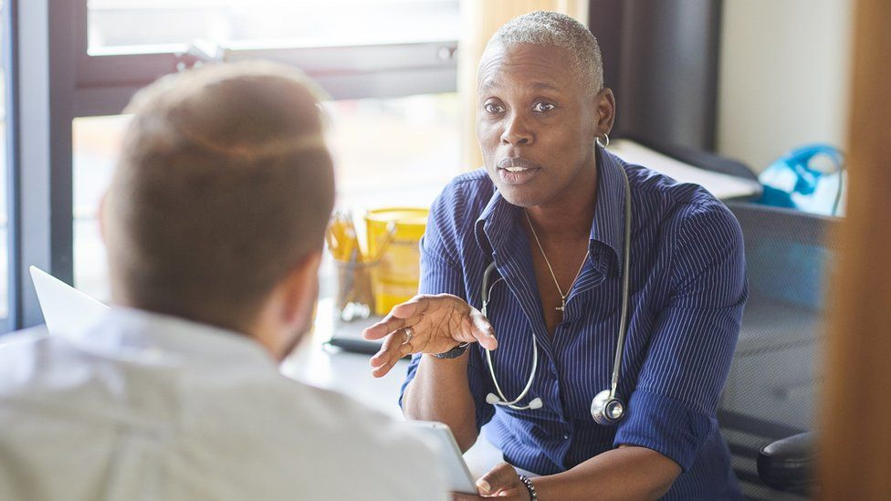 A GP chats to a patient