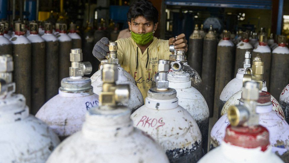 Worker arranges oxygen cylinders for transport to hospital in Hyderabad, India (23 April)