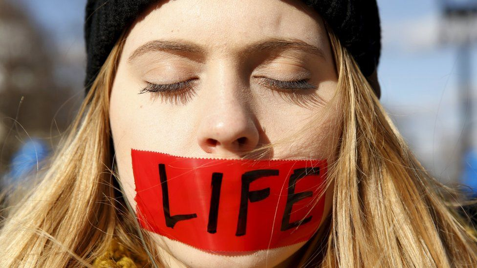 "A protester with her mouth taped over with the word ""life"" stands in front of the US Supreme Court"