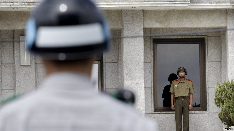 A North (R) and a South Korean army soldier stand guard, in Paju, South Korea, June 26, 2015.