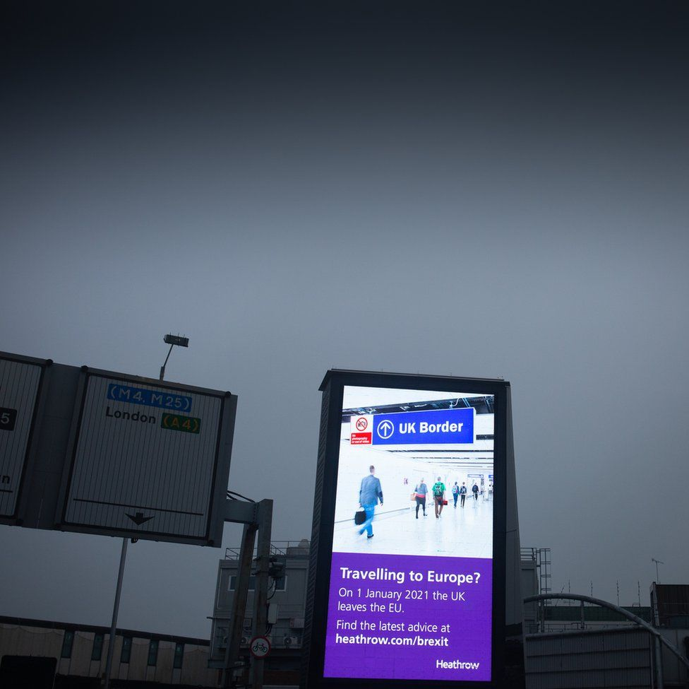 An image of a motorway sign next to a sign giving people Covid travel instructions