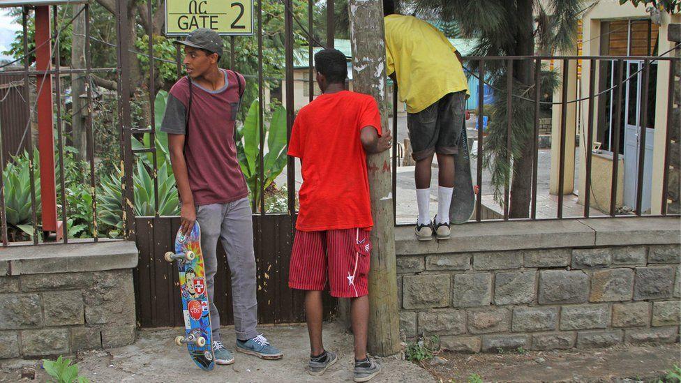 Boys peer through gate of skatepark