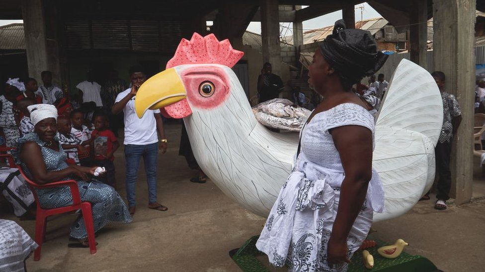 A woman touching a coffin that is shaped like a rooster