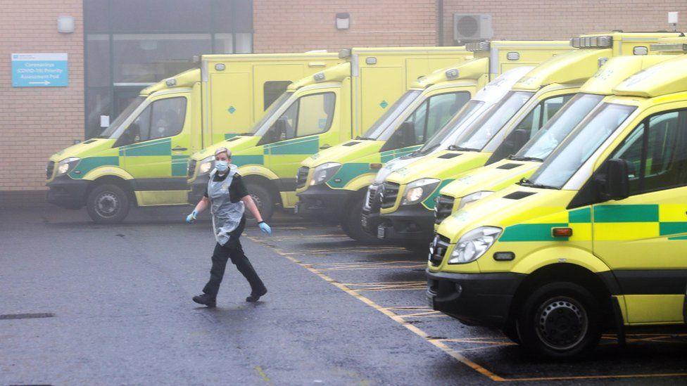 An paramedic walks past a row of ambulances outside a hospital