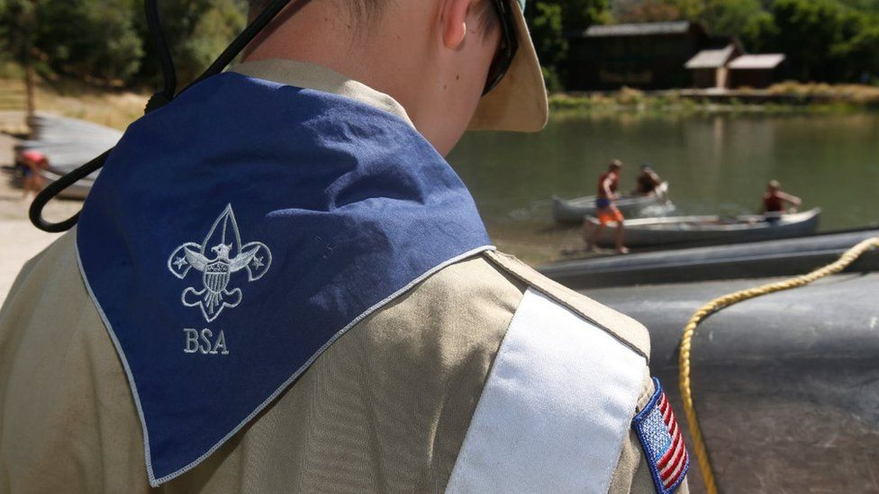 A Boy Scout of America stands with his back to the camera