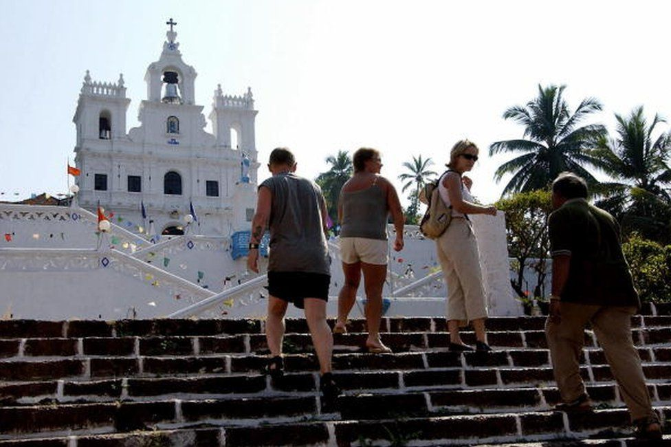 International tourists with an Indian guide walk up the steps towards Saint Mary's Church in Panjim, the capital city of Old Goa, some 615 kms south of Bombay, 01 December 2003. Latest figures show there is a substantial increase in the number of visitors arriving in India with Goa being one of the most popular destinations for tourists.