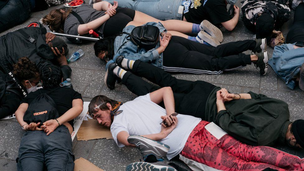 Protesters lie on the ground with their hands behind their backs