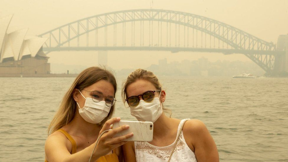 Two German tourists pose for a selfie, wearing breathing masks, as heavy smoke blankets Sydney skyline