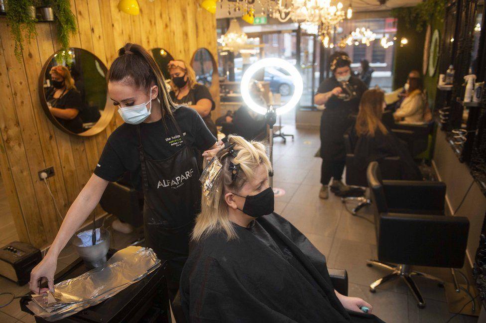 A woman getting her hair cut in a salon in Belfast