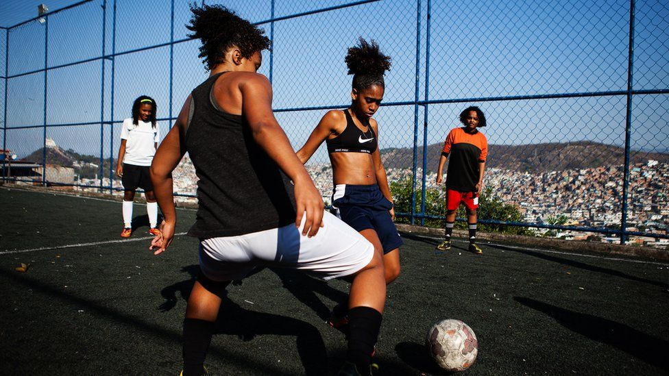 Competitive training on the field, as one girl attempts to evade a tackle from her training partner