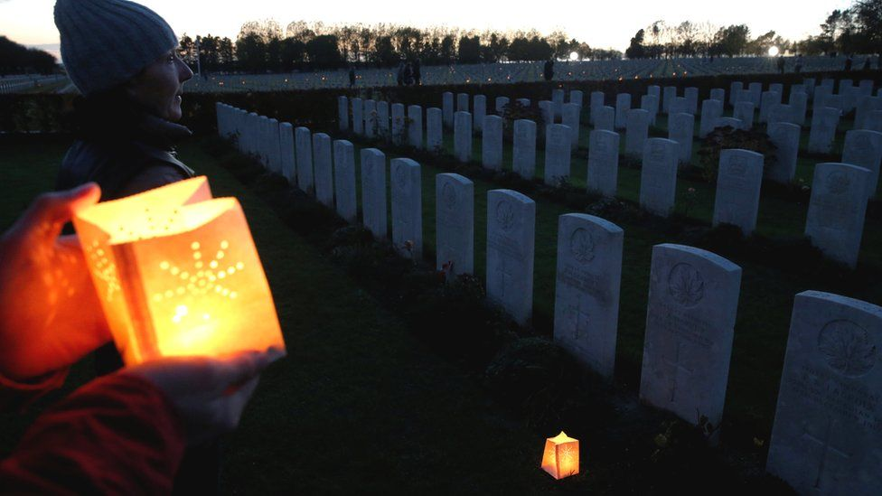 People place candles at the graves of soldiers killed during World War One, at La Targette British Cemetery in Neuville-Saint-Vaast, France, 10 November 2018