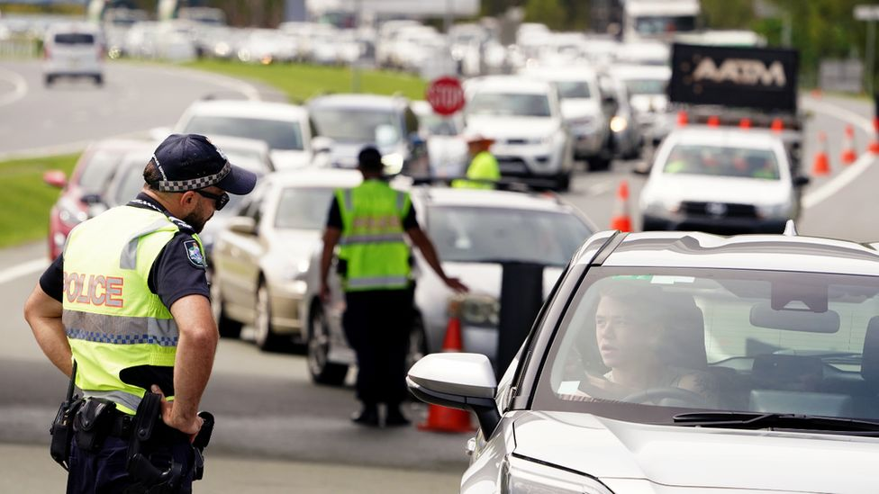 Police checking the border entry requirements of car passengers waiting to cross into Queensland from New South Wales