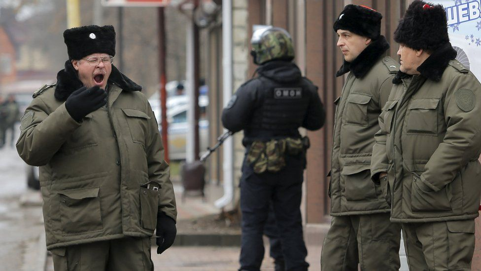Russian Cossacks and police officer stand guard during hearing of former Ukrainian army pilot Nadiya Savchenko near in the southern border town of Donetsk in Rostov region, Russia. 22 March 2016