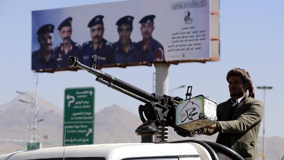 Houthi fighter stands behind a vehicle-mounted machine gun in Sanaa, Yemen (19 December 2018)