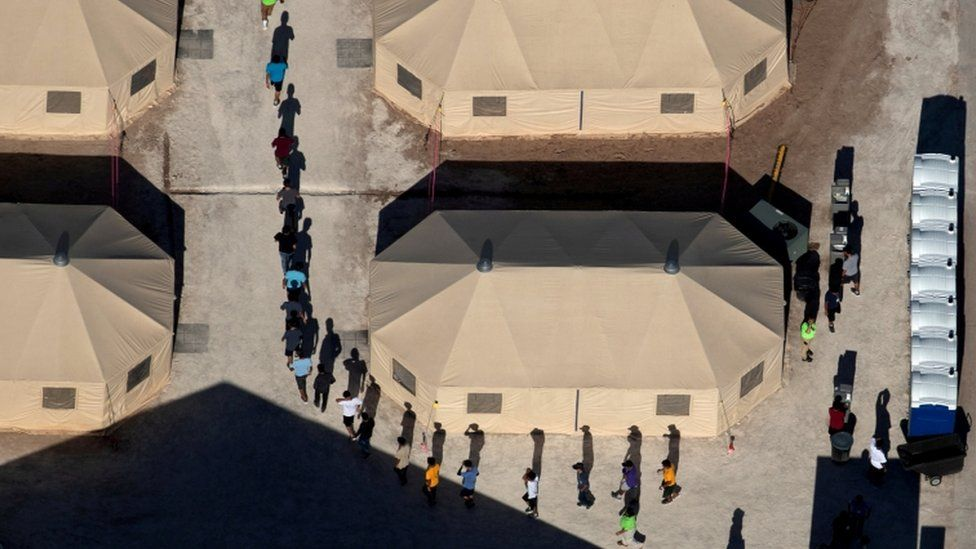 mmigrant children are led by staff in single file between tents at a detention facility next to the Mexican border in Tornillo, Texas, U.S., June 18, 2018.