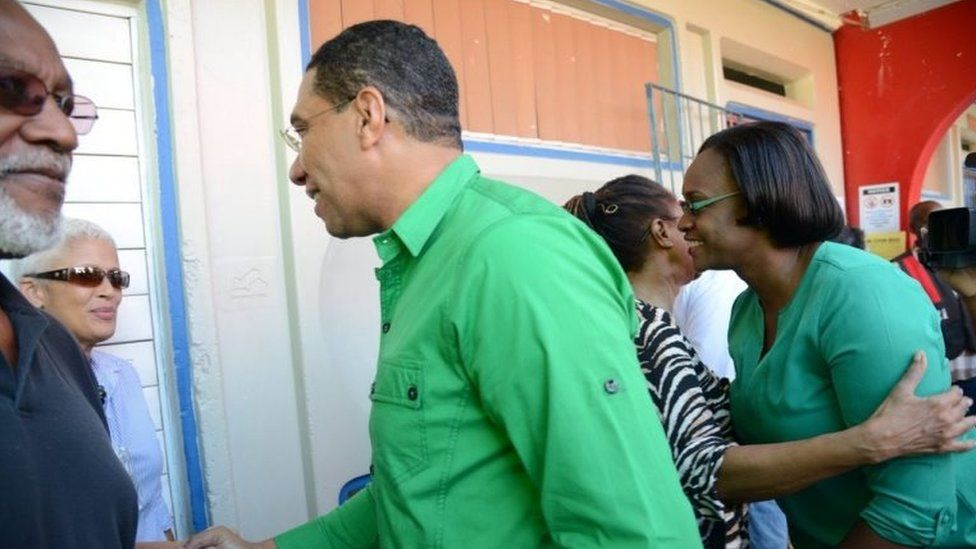 Opposition Leader Andrew Holness (centre) and his wife Juliet (right) greets voters at the Mona high school polling station on Election Day in Kingston, Jamaica, 25 February 2016.