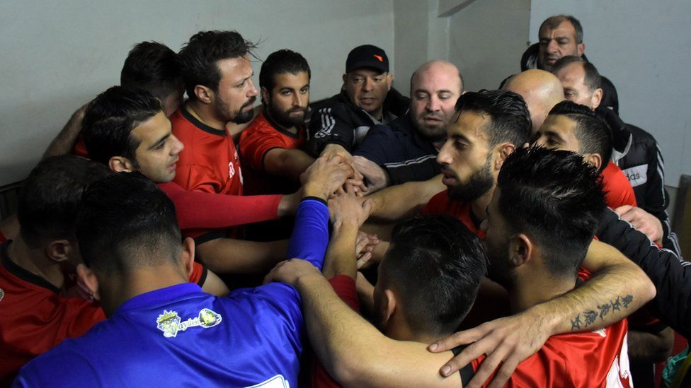 Al-Ittihad players huddle in the dressing room before the game