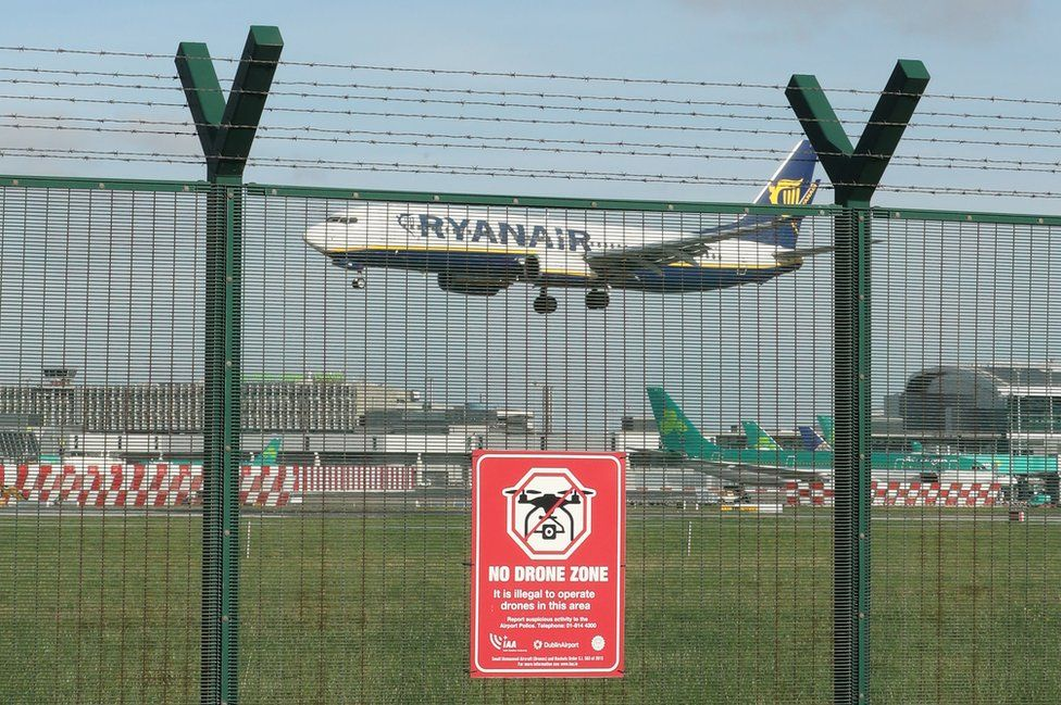 A plane flying into Dublin Airport behind a fence with a sign that reads: No drone zone