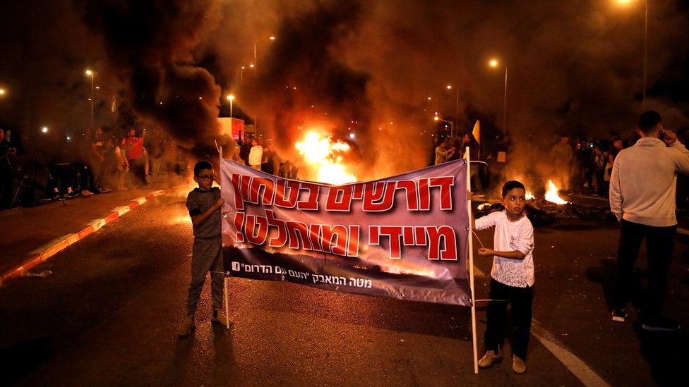 Protesters in Sderot, Israel, set fire to tyres and hold up banners to protest against the Israeli government's decision to agree to a ceasefire with Palestinian militants in Gaza (13 November 2018)
