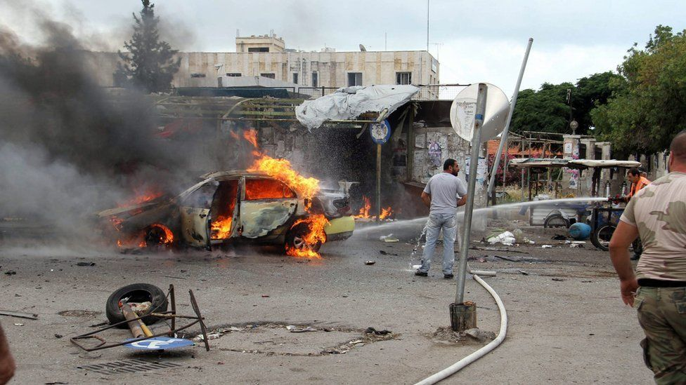 Firefighters tackle burning vehicle following bombing at bus station in coastal city of Tartous, Syria, 23 May 2016