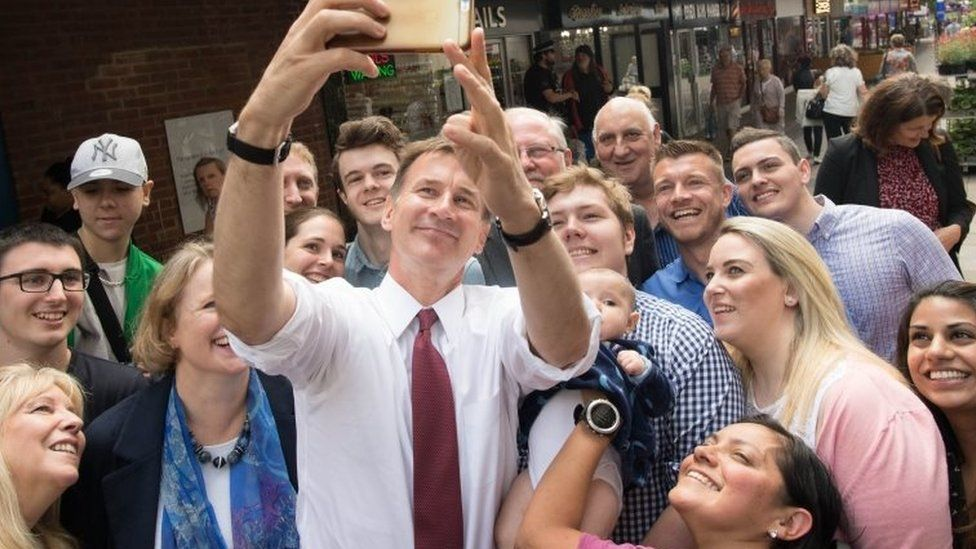Jeremy Hunt taking a selfie with a crowd of people