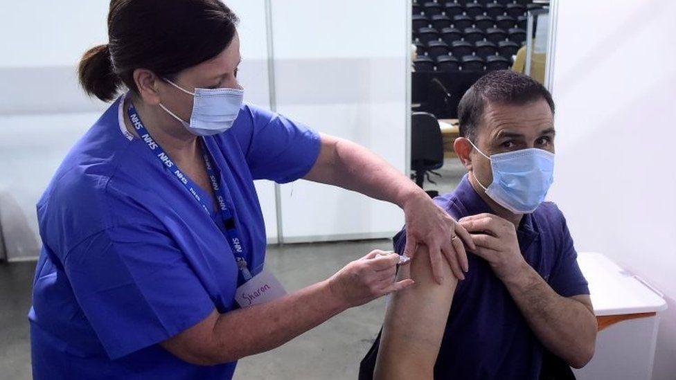 A man receiving a dose of the AstraZeneca vaccine