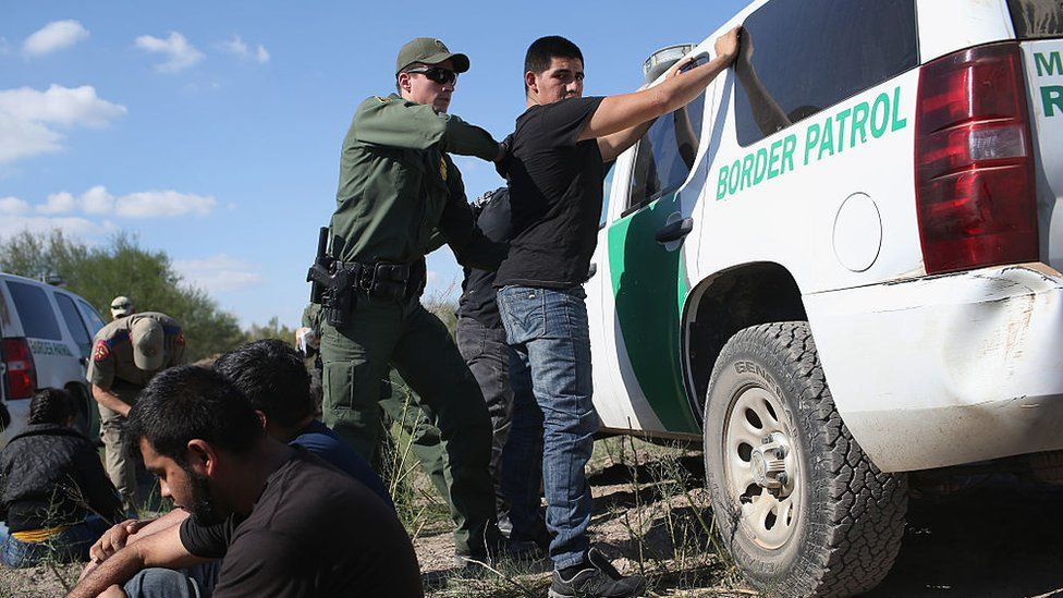 A US Border Patrol officer body searches an undocumented immigrant after he illegally crossed the U.S.-Mexico border
