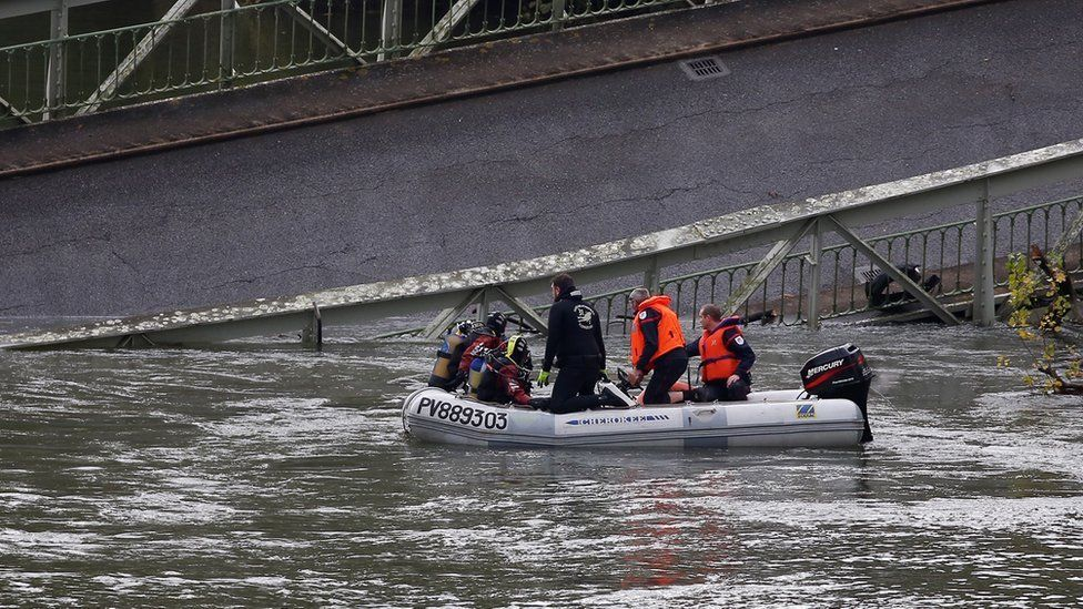Rescuers at work to recover victims after a suspension bridge collapsed over the Tarn river