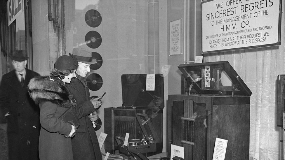 A couple looking at radios in the window of HMV in 1937