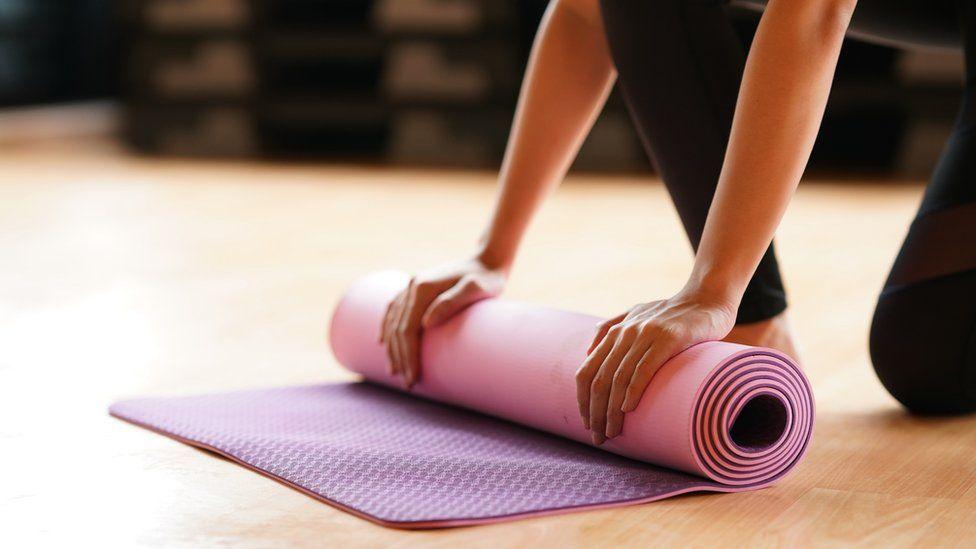 A woman rolls a yoga mat