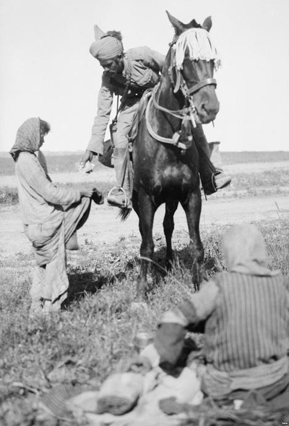 Indian cavalryman hands rations to starving Christian girls