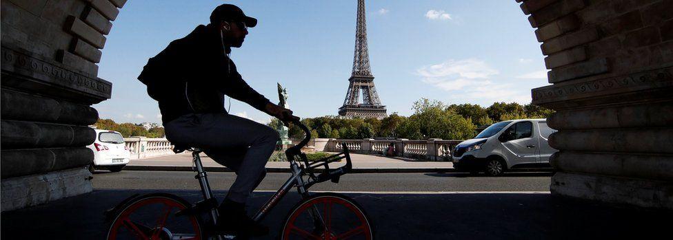 A commuter rides a bike-sharing service mobike bicycle at the Pont de Bir-Hakeim bridge near the Eiffel Tower