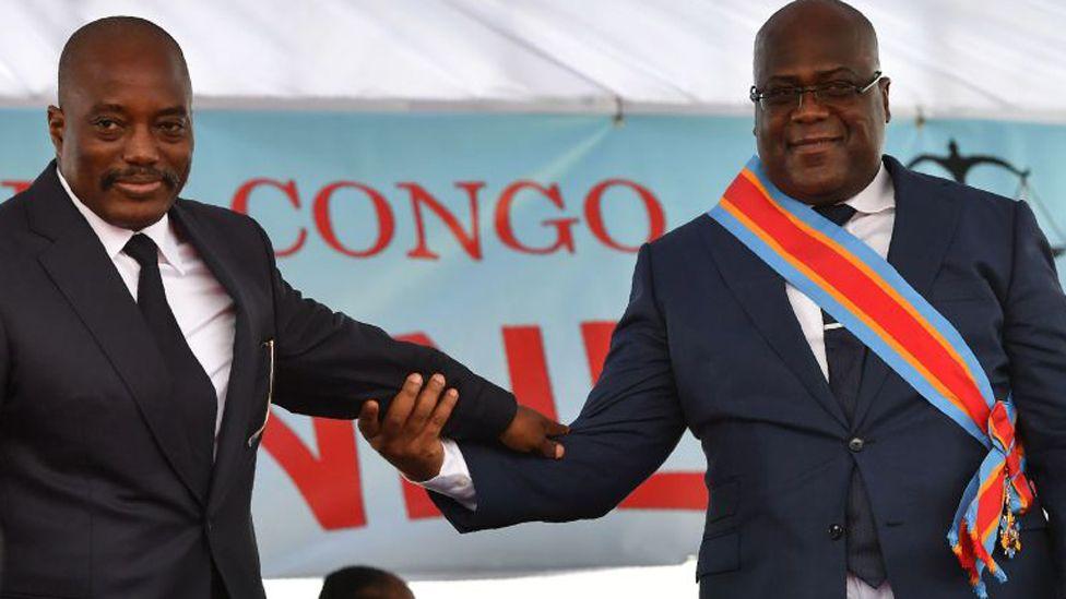 Democratic Republic of the Congo's newly inaugurated President Felix Tshisekedi (R) walks off the podium with outgoing President Joseph Kabila