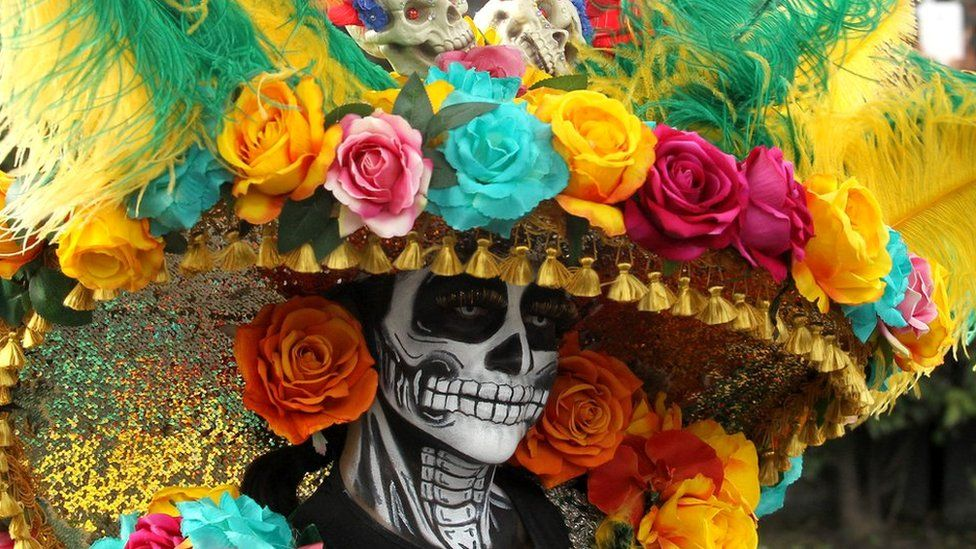 A woman with skeleton make-up has a large floral hat on