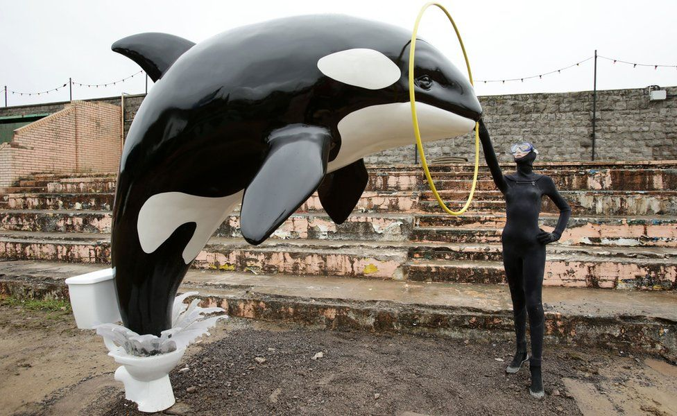 A Banksy piece depicting an orca whale jumping out of a toilet is displayed at Dismaland