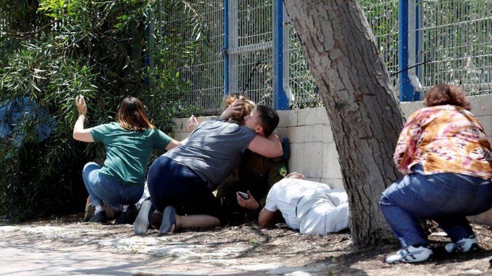 Israelis crouching down in Ashkelon