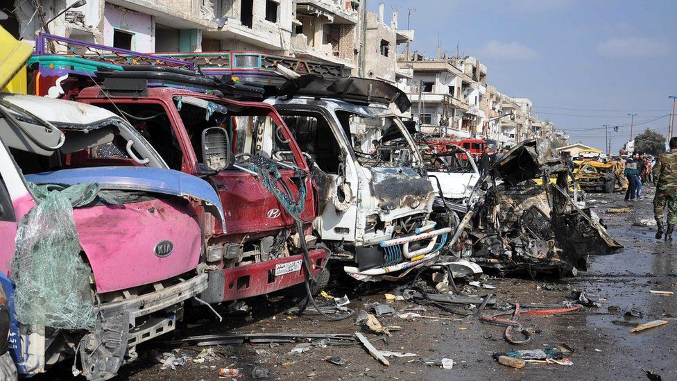 Damaged cars and buildings are seen at the site of a twin bomb attack in the city of Homs, Syria, 21 February 2016