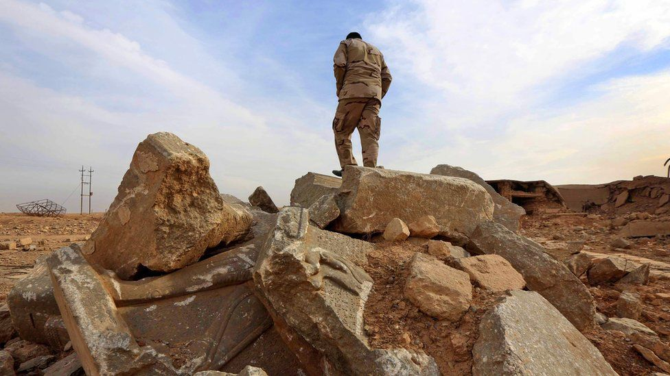 An Iraqi soldier stands on ruins of the archaeological site of Nimrud