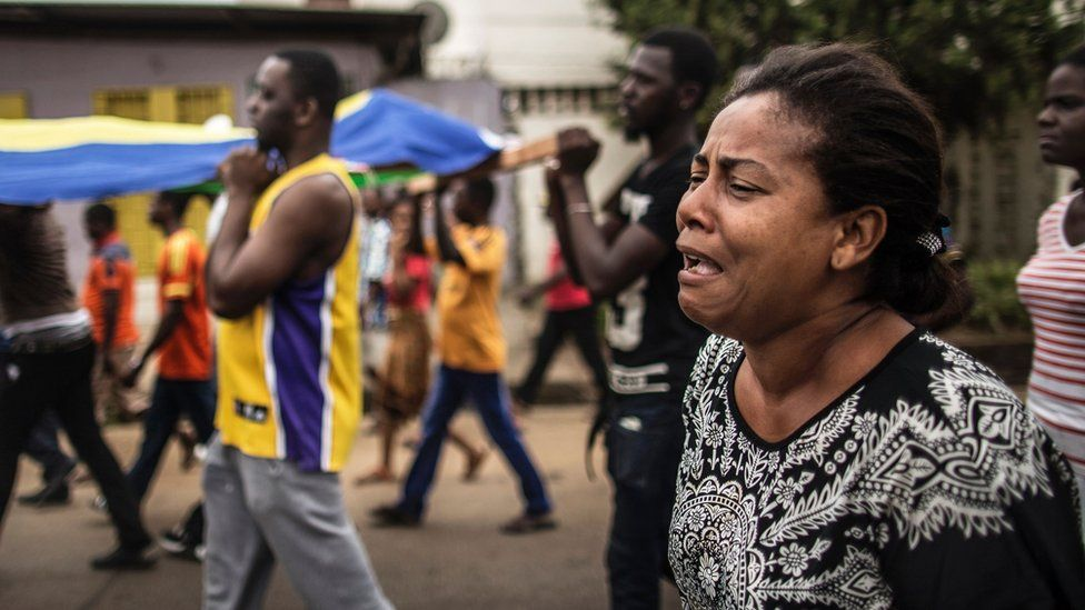 Protesters carry the body of Axel Messa, 30, wrapped in the flag of Gabon, in a street of the Libreville district of Nzeng Ayong, 2 September 2016