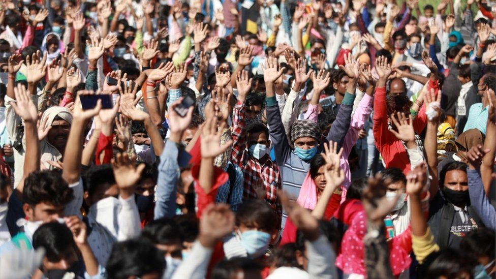 Migrant workers raise their hands as policemen ask them for their destination as they wait for buses along a highway with their families as they return to their villages, during a 21-day nationwide lockdown to limit the spreading of coronavirus disease (COVID-19), in Ghaziabad, on the outskirts of New Delhi, India, 28 March 2020.