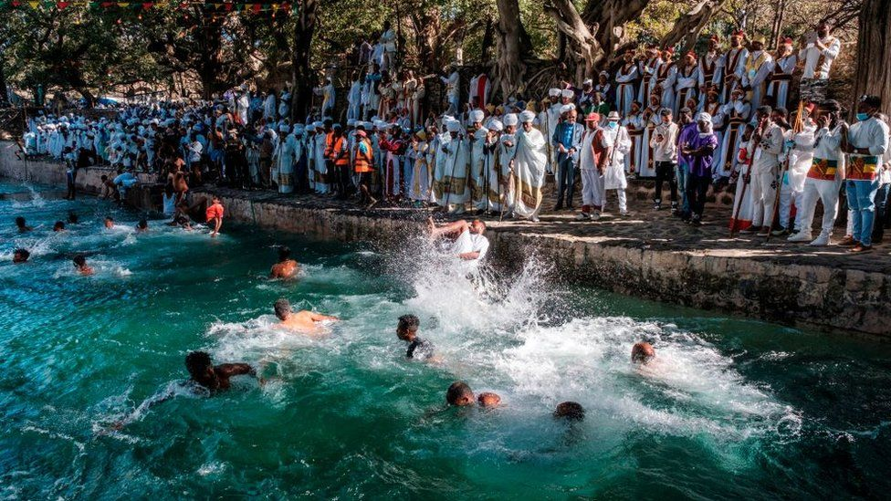 Ethiopian Orthodox Christian worshippers swim in the pool of Fasilides Bath during the celebration of Timkat, the Ethiopian Epiphany, in the city of Gondar, Ethiopia, on January 19, 2021. - Timkat is the Ethiopian Orthodox Christian festival which celebrates the baptism of Jesus in the Jordan river. The celebration has been recently declared Intangible Human Heritage by UNESCO.