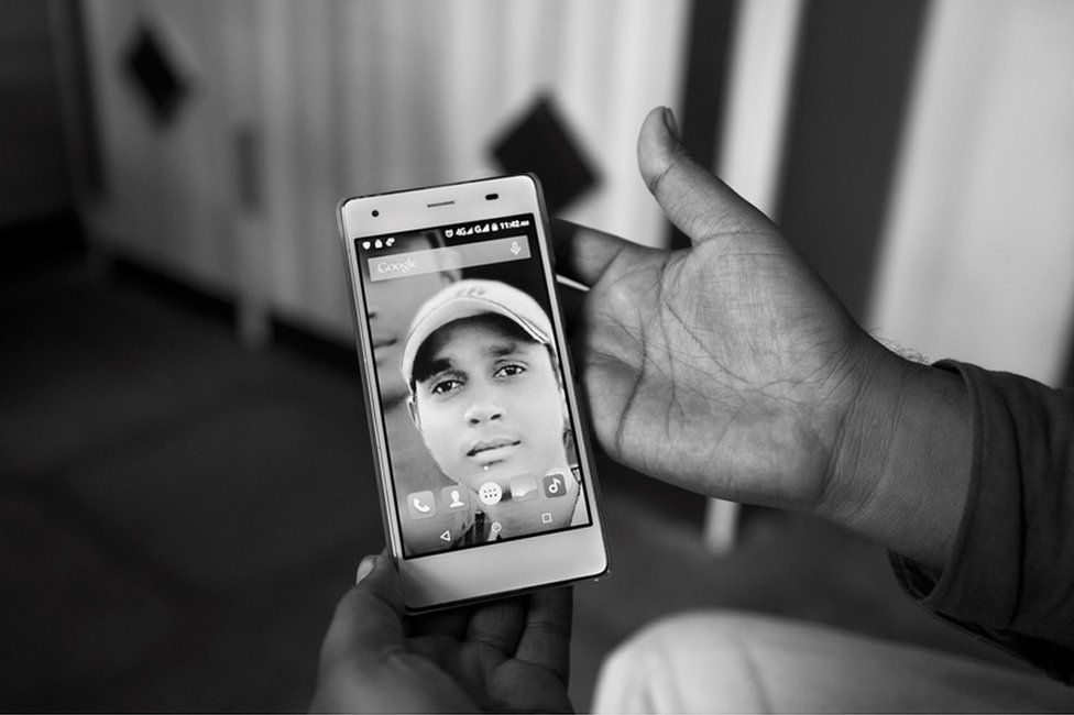 A family member holding Sagar Shejwal's photo.