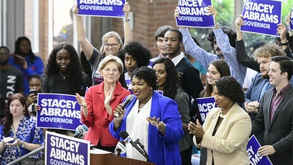 Stacey Abrams speaks to supporters, joined by Boston City Councilwoman Ayanna Presseley (R) and Democratic Senator Elizabeth Warren of Massachusetts.