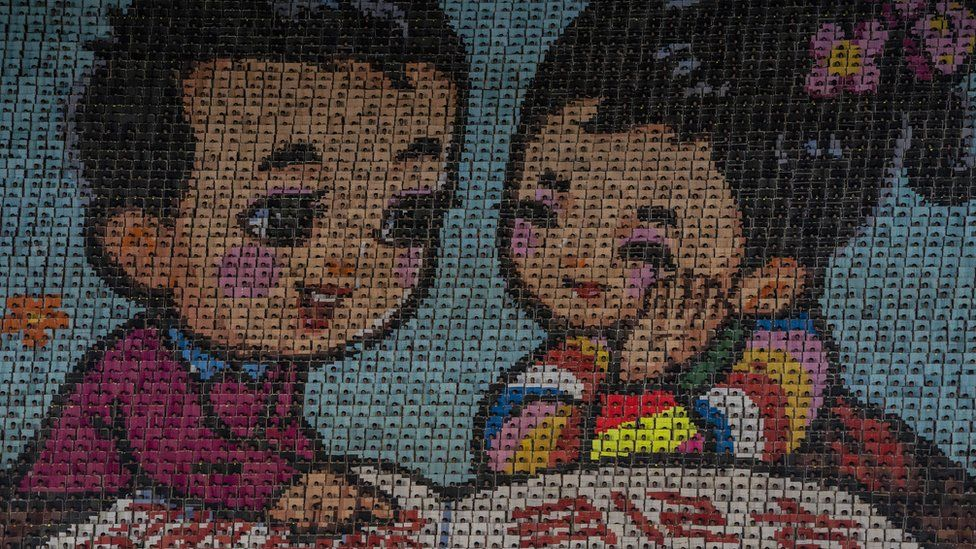 A 'moving image' wall of 17,490 schoolchildren creating a mosaic of a boy and a girl
