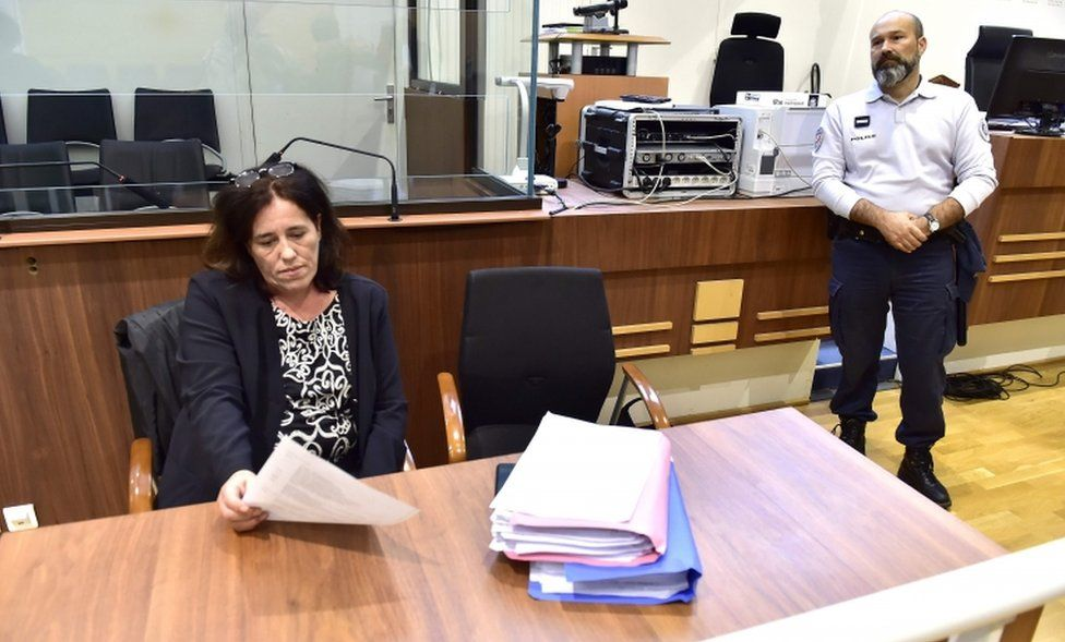 Rosa Maria Da Cruz sits reading a sheet of paper during her trial at the Assize Court of Tulle, central France
