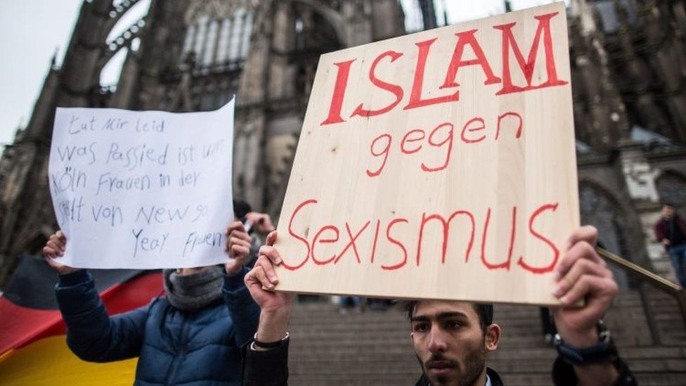 """A man from Syria carries a sign that reads """"Islam against sexism"""" in front of the central railway station in Cologne (10 January 2016)"""
