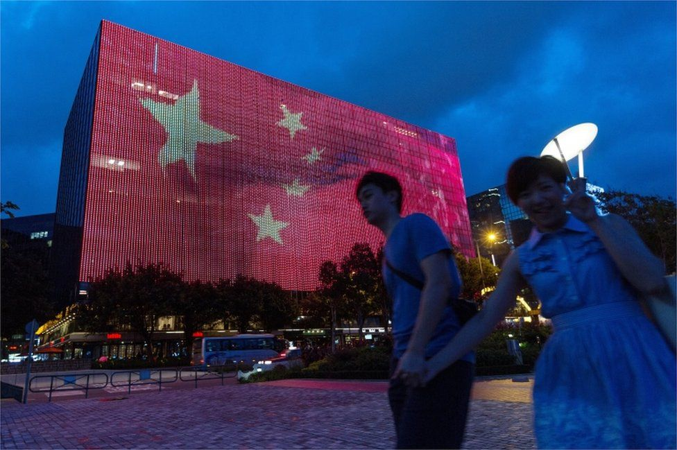 A couple walk past a giant electronic billboard showing a Chinese flag on the side of a building in Tsim Sha Tsui, Hong Kong, on 24 June 2017.